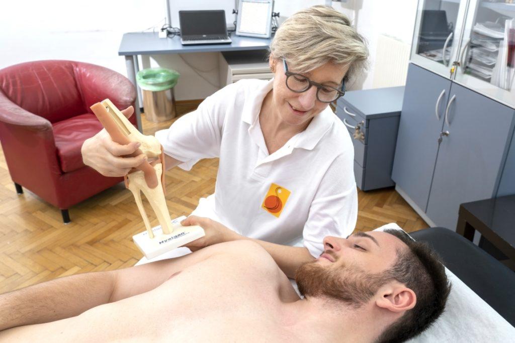 dr martha schmid erklärt einem Patienten ein Gelenk