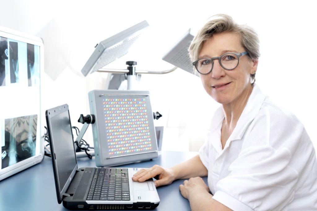 dr martha schmid sitzt am Notebook und sieht richtung kamera